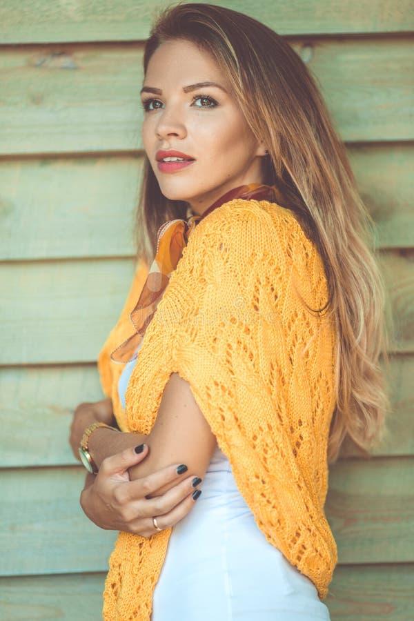 La mujer sonriente de la moda está llevando el suéter amarillo sobre fondo de madera al aire libre fotografía de archivo libre de regalías