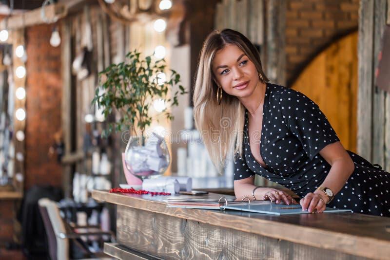La mujer sonriente del Admin lleva a cabo su mano en el menú del servicio y con una sonrisa saluda a clientes imágenes de archivo libres de regalías