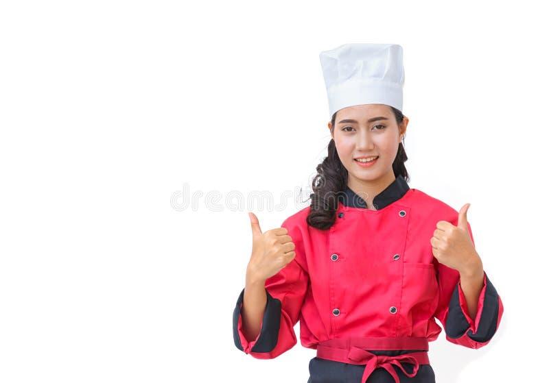 La mujer sonriente del cocinero en mostrar uniforme del rojo manosea con los dedos encima del aislador del gesto foto de archivo