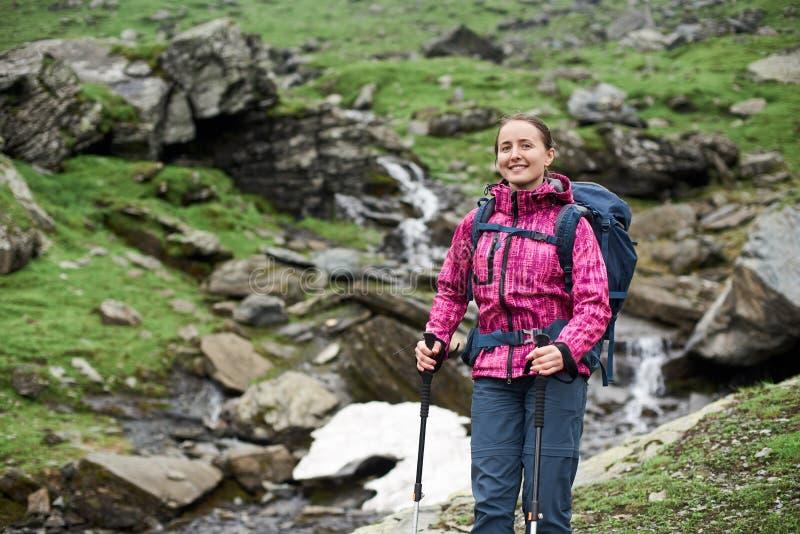 La mujer sonriente del primer con la mochila y emigrar se pega en montañas imagen de archivo