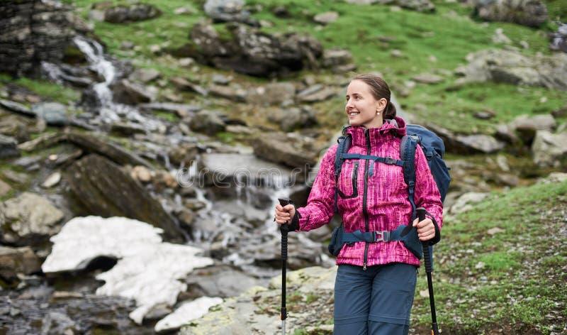 La mujer sonriente del primer con la mochila y emigrar se pega en montañas imágenes de archivo libres de regalías