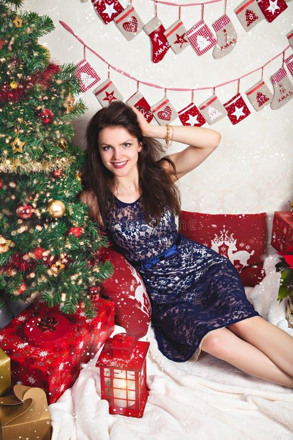 La mujer sonriente en cordón festivo se viste entre la decoración de la Navidad imágenes de archivo libres de regalías