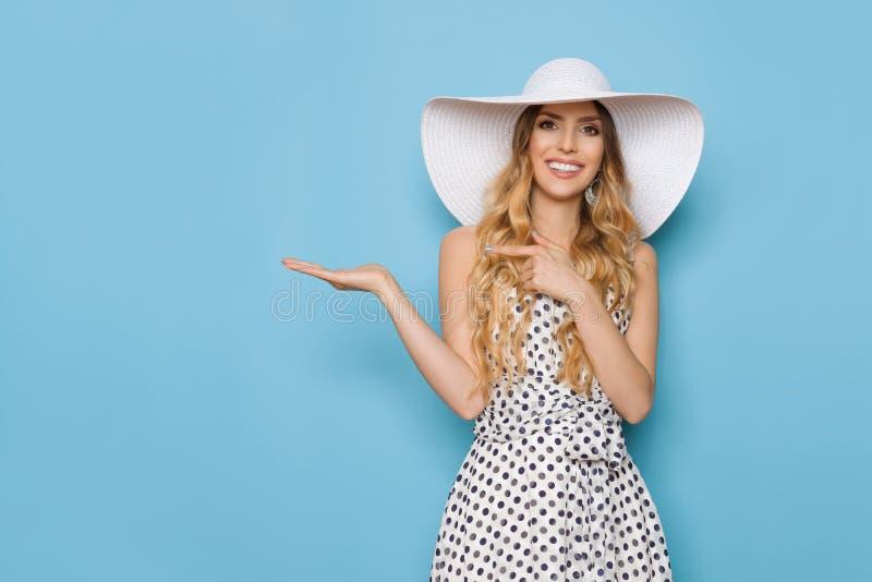 La mujer sonriente en el sombrero blanco de Sun del verano está presentando y está señalando fotos de archivo