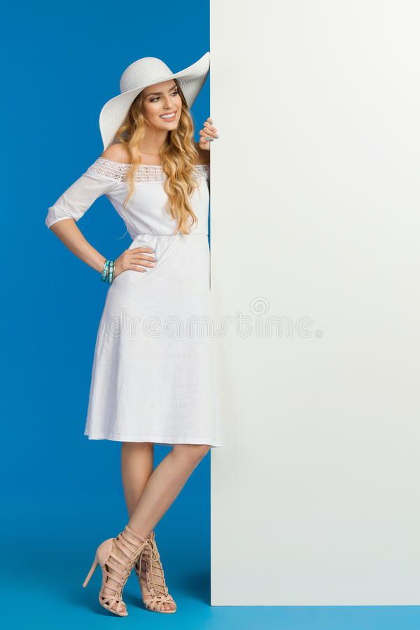 La mujer sonriente en el vestido del verano y el sombrero blancos de Sun se está colocando cerca de una bandera y de una lectura fotos de archivo libres de regalías