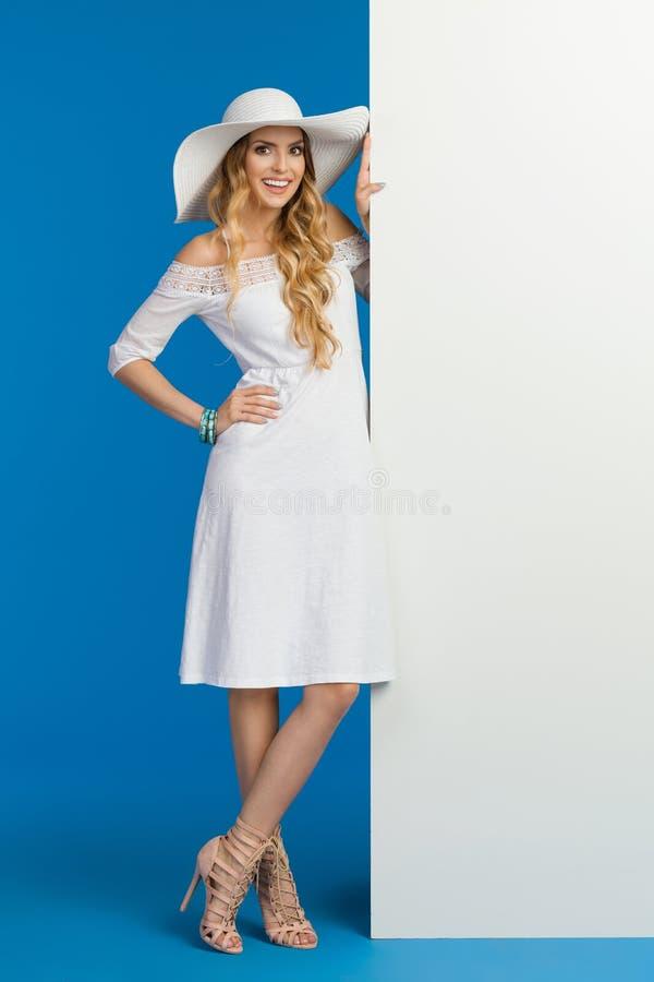La mujer sonriente en el vestido y el sombrero blancos del verano está presentando cerca de una bandera foto de archivo