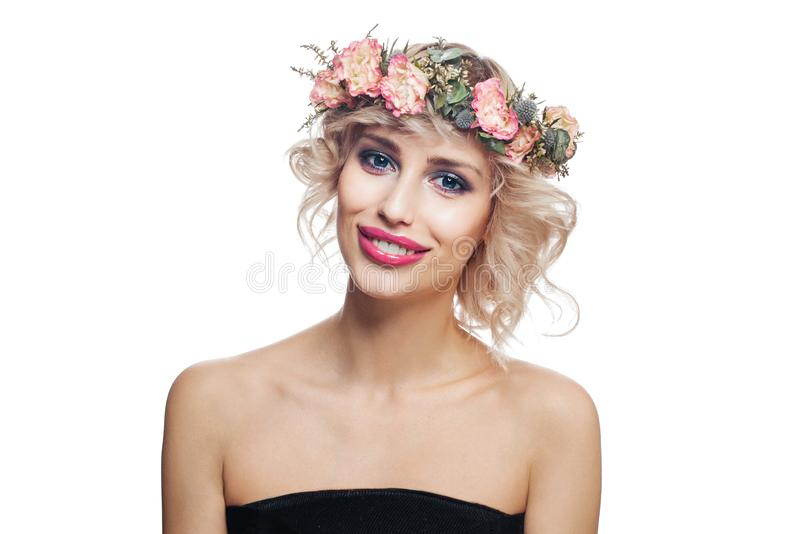 La mujer sonriente en flores corona Modelo joven con el pelo rizado rubio corto y maquillaje aislados en el fondo blanco fotos de archivo