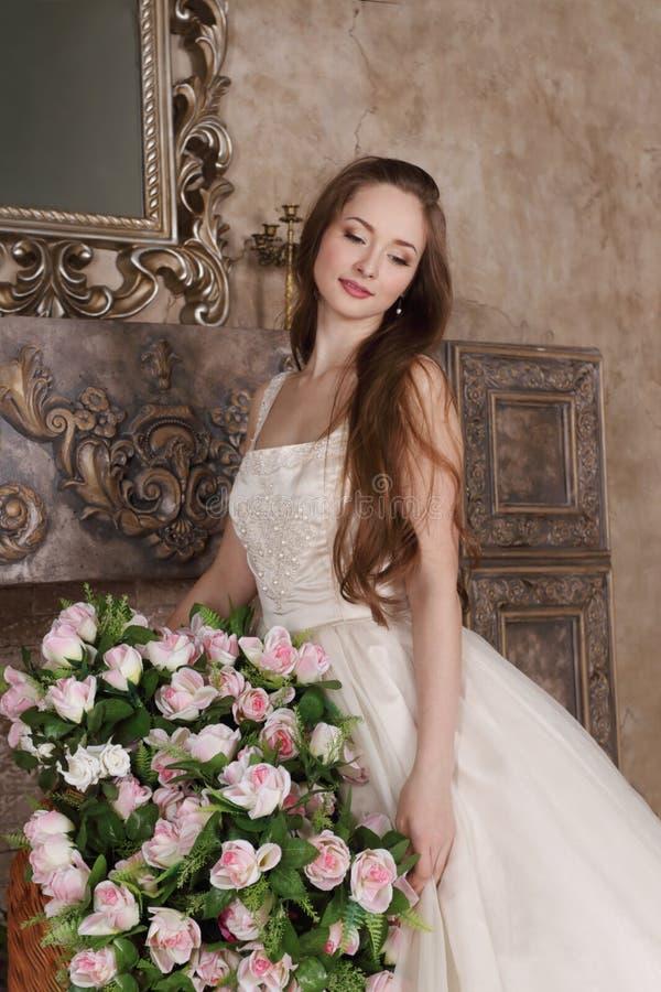 La mujer sonriente en vestido largo sostiene la cesta de flores imagenes de archivo