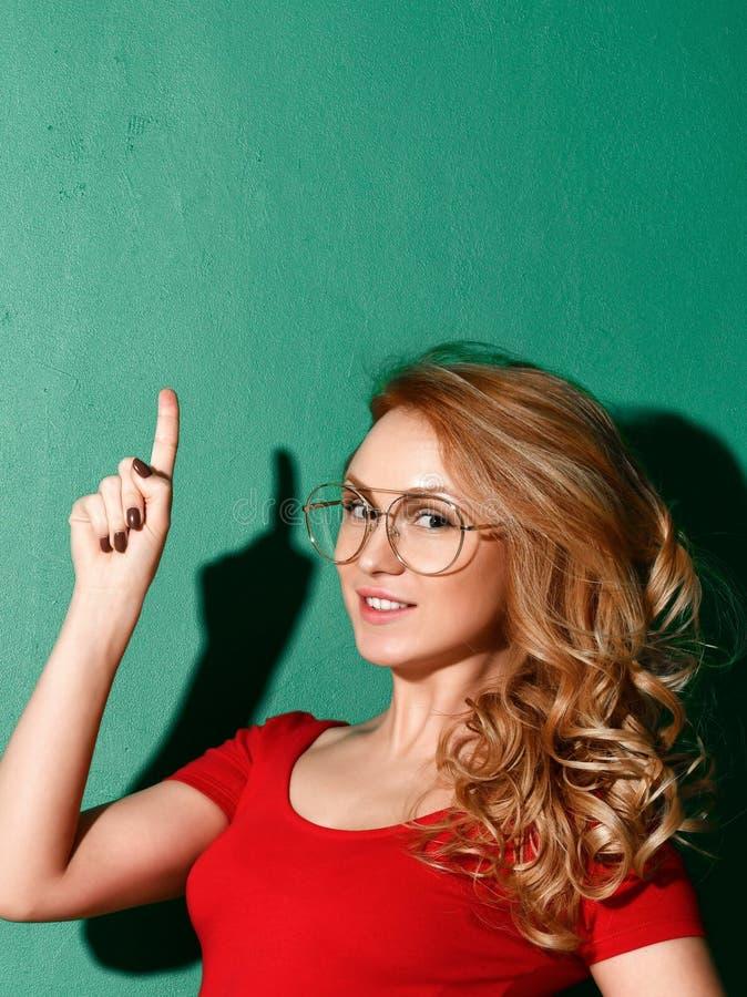 La mujer sonriente está señalando el finger encima de la idea firma adentro la camiseta roja en fondo verde fotos de archivo libres de regalías