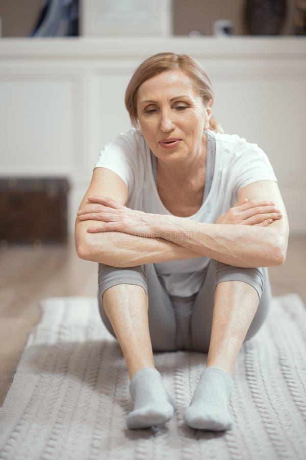La mujer sonriente está teniendo un resto que se sienta después de practicar yoga fotografía de archivo libre de regalías