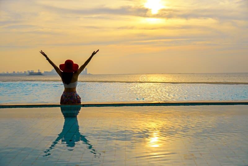 La mujer sonriente feliz de Asia con el sombrero de paja se relaja y lujo en piscina, puesta del sol del fondo fotografía de archivo libre de regalías