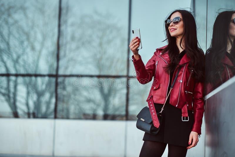 La mujer sonriente feliz en chaqueta y gafas de sol rojas est? disfrutando de caminar afuera mientras que toma el selfie en su te imagenes de archivo