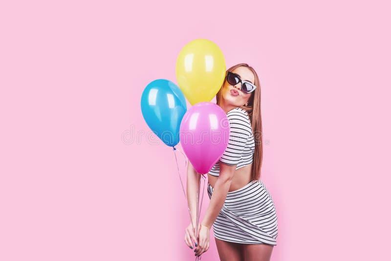 La mujer sonriente feliz está mirando en los globos coloridos de un aire que se divierten sobre un fondo rosado foto de archivo