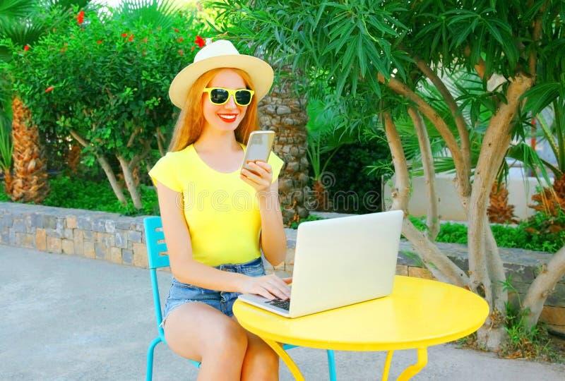La mujer sonriente feliz está trabajando con el smartphone, ordenador portátil imagen de archivo libre de regalías