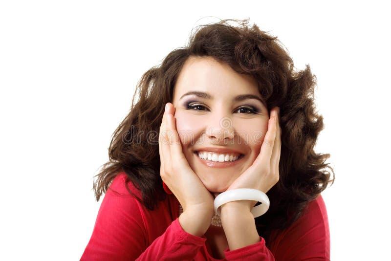 La mujer sonriente feliz joven hermosa con las manos acerca a su cara foto de archivo