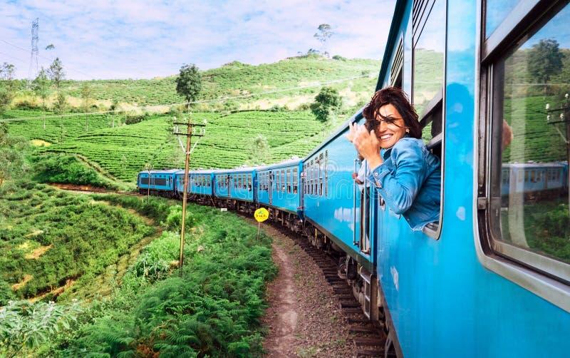 La mujer sonriente feliz mira hacia fuera de la ventana que viaja en tren encendido fotos de archivo libres de regalías