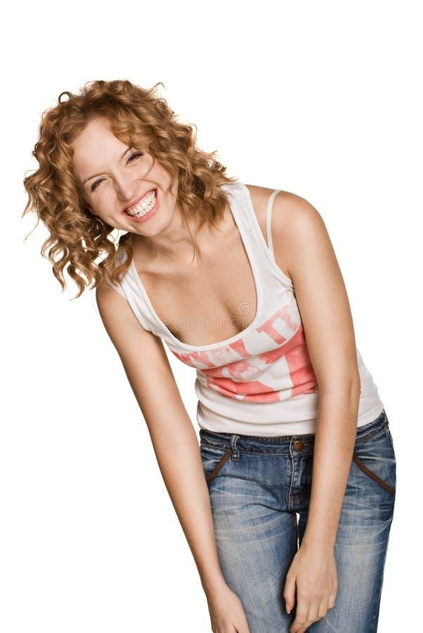 La mujer sonriente feliz se vistió en pantalones vaqueros imagenes de archivo