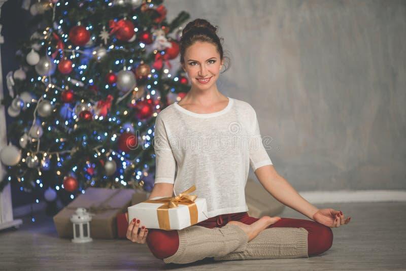 La mujer sonriente flexible hermosa con la caja de regalo está haciendo estirando el árbol cerca en casa adornado de Navidad de l fotografía de archivo