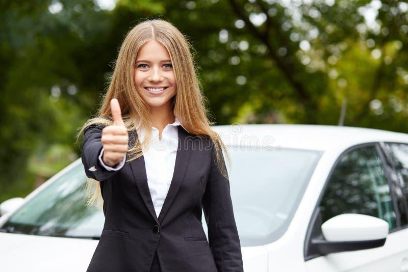 La mujer sonriente hace gesto con el pulgar para arriba fotografía de archivo
