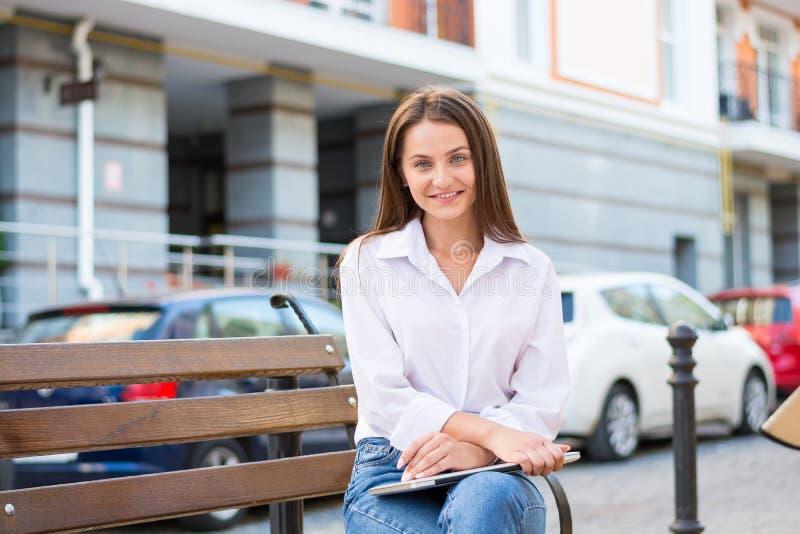 La mujer sonriente hermosa joven, freelancer, trabaja en el ordenador portátil i fotos de archivo
