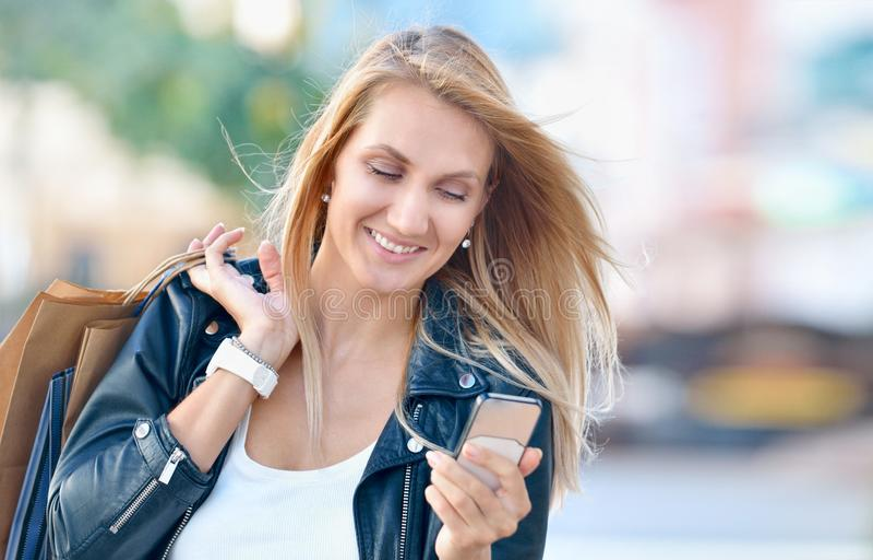 La mujer sonriente joven con los bolsos shoping mira el teléfono portátil fotos de archivo libres de regalías