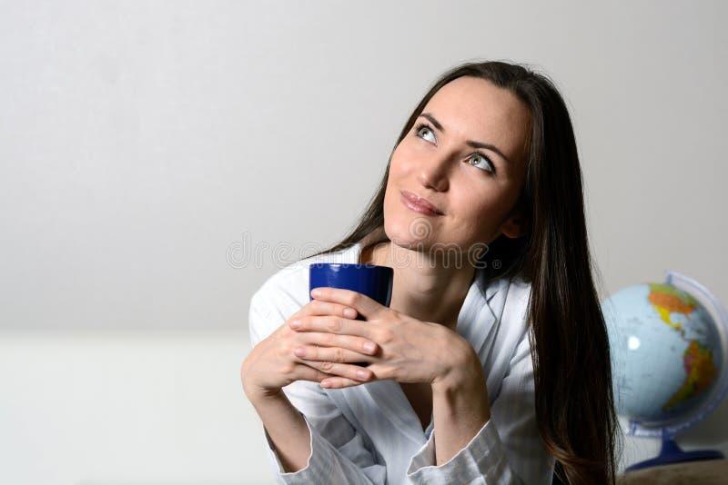 La mujer sonriente joven con una taza azul de café o de té, sentándose en el sofá en el cuarto y quiere descansar, marido, nueva  foto de archivo libre de regalías