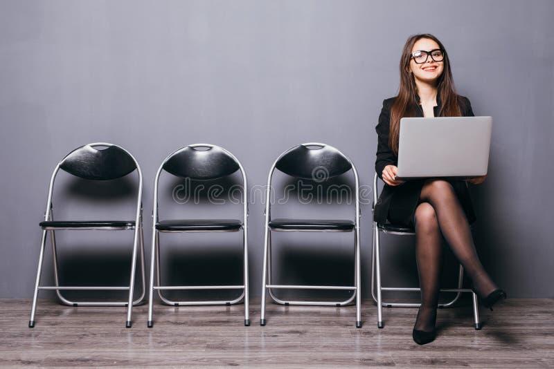 La mujer sonriente joven del oficinista que se sienta en la silla de madera del piso usando el ordenador portátil móvil prepara e foto de archivo libre de regalías