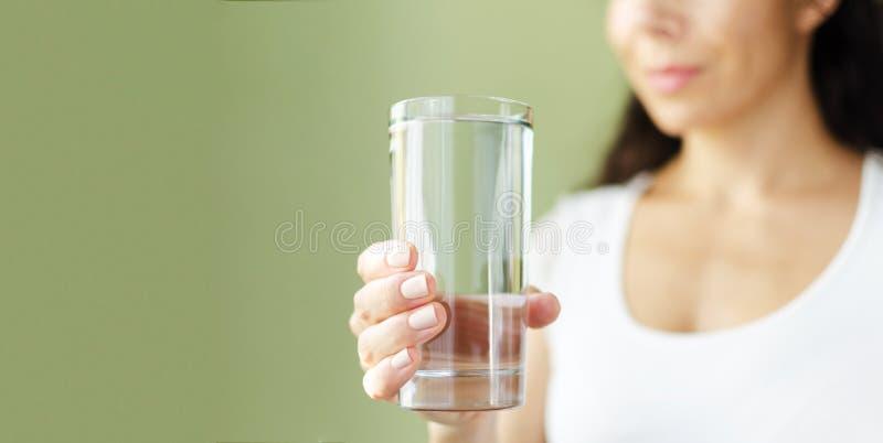 La mujer sonriente joven en la camiseta blanca sostiene hacia fuera el vidrio de agua Fondo verde Copie el espacio imagenes de archivo