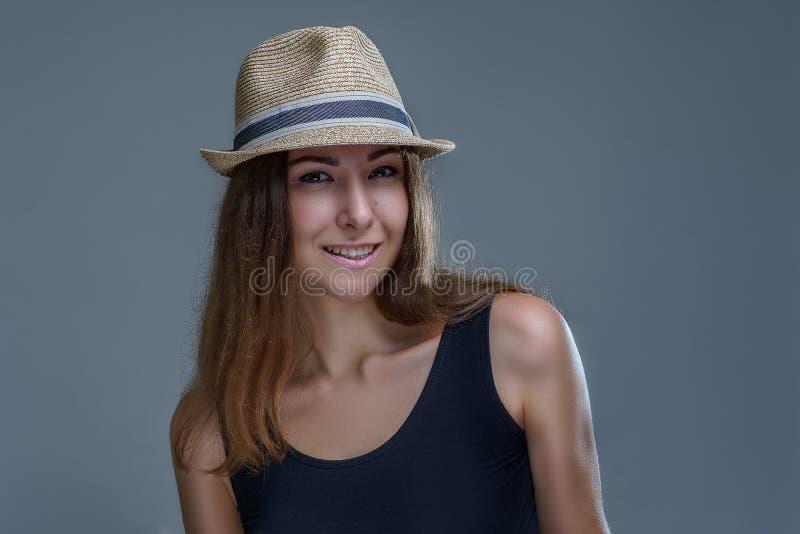 La mujer sonriente joven hermosa en sombrero y camisa negra presentando está aislando elegante en fondo gris en un cierre del est imagenes de archivo