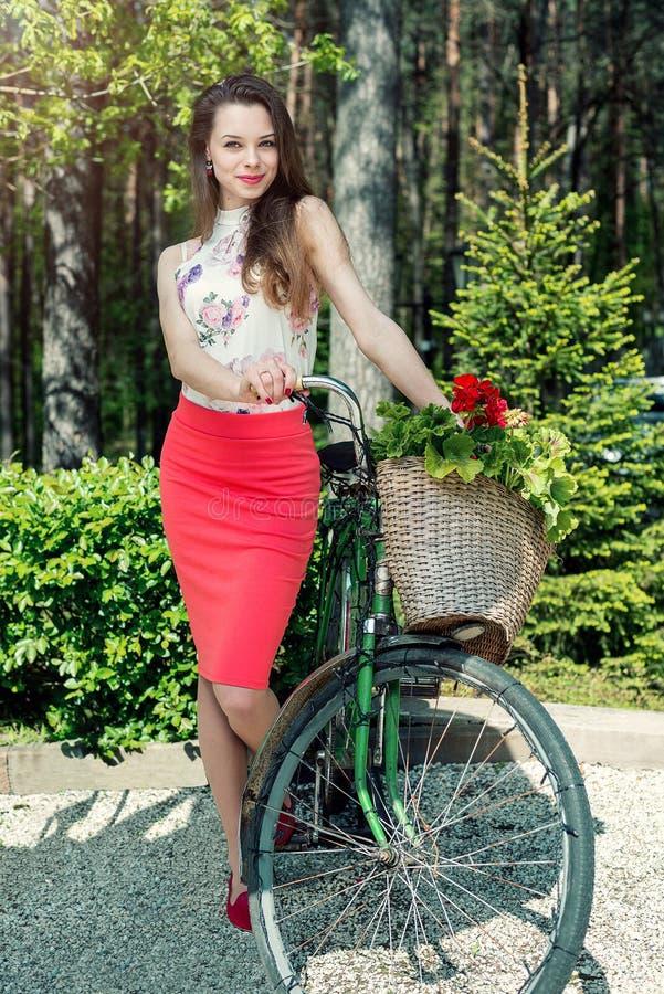 La mujer sonriente joven monta una bicicleta con una cesta llena de flor fotografía de archivo