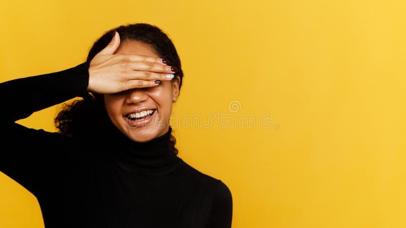 La mujer sonriente joven la oculta los ojos con la palma imagenes de archivo
