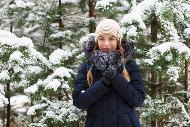 La mujer sonriente joven que lleva el borde de piel real encapuchado azul abajo cubre disfrutar de la visión en bosque del invier fotografía de archivo libre de regalías