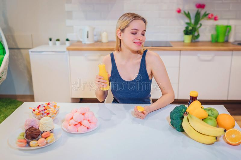 La mujer sonriente joven sostiene el agua del detox mientras que elige entre la comida sana y malsana en la cocina Opción difícil fotos de archivo libres de regalías