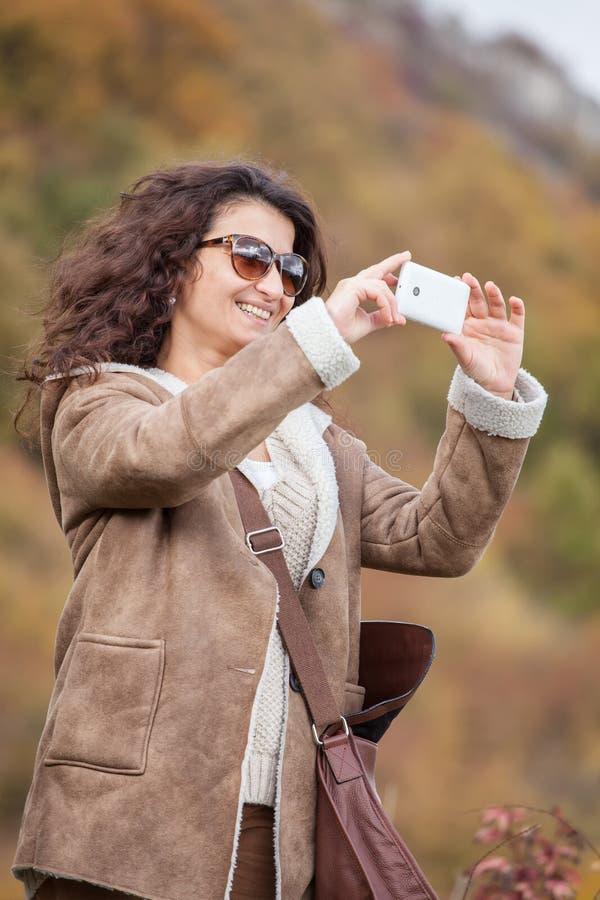 La mujer sonriente joven toma la foto con el teléfono móvil en bosque del otoño imágenes de archivo libres de regalías