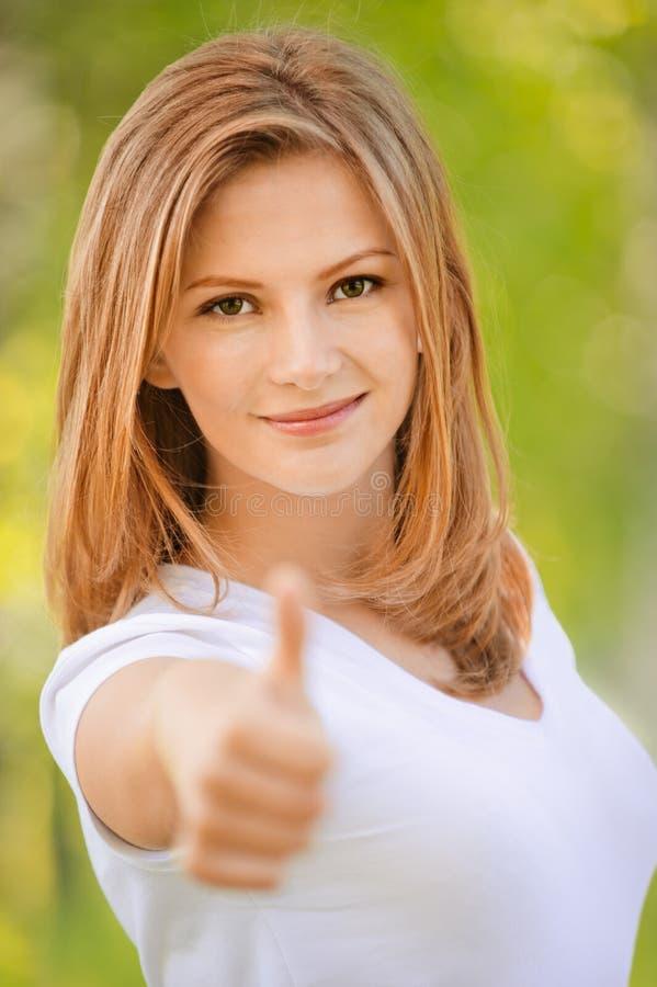 La mujer sonriente levanta el pulgar imagen de archivo libre de regalías