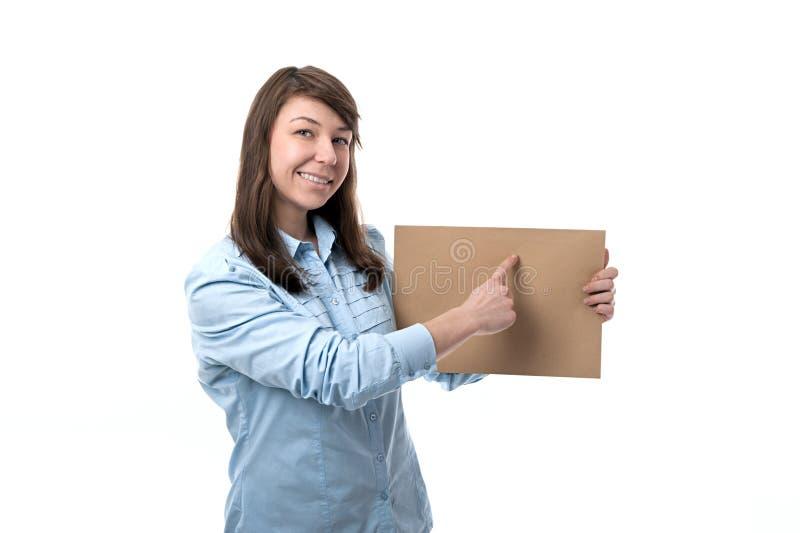 La mujer sonriente muestra el papel imagenes de archivo