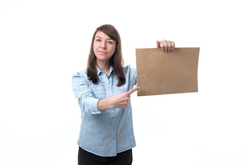 La mujer sonriente muestra el papel imagen de archivo