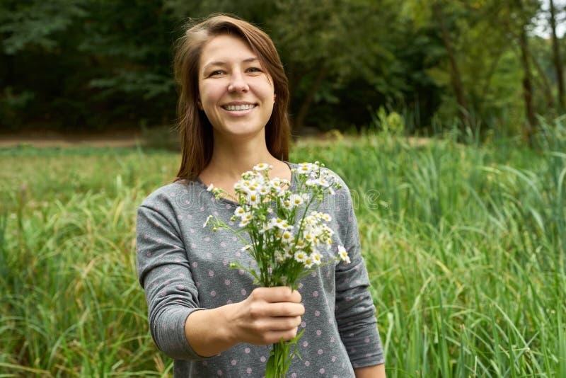 La mujer sonriente presenta un ramo de margaritas imagen de archivo