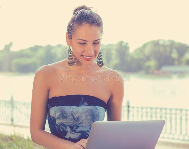La mujer sonriente que enviaba los correos electrónicos que se sentaban en hierba con el ordenador equilibró en rodillas imagenes de archivo