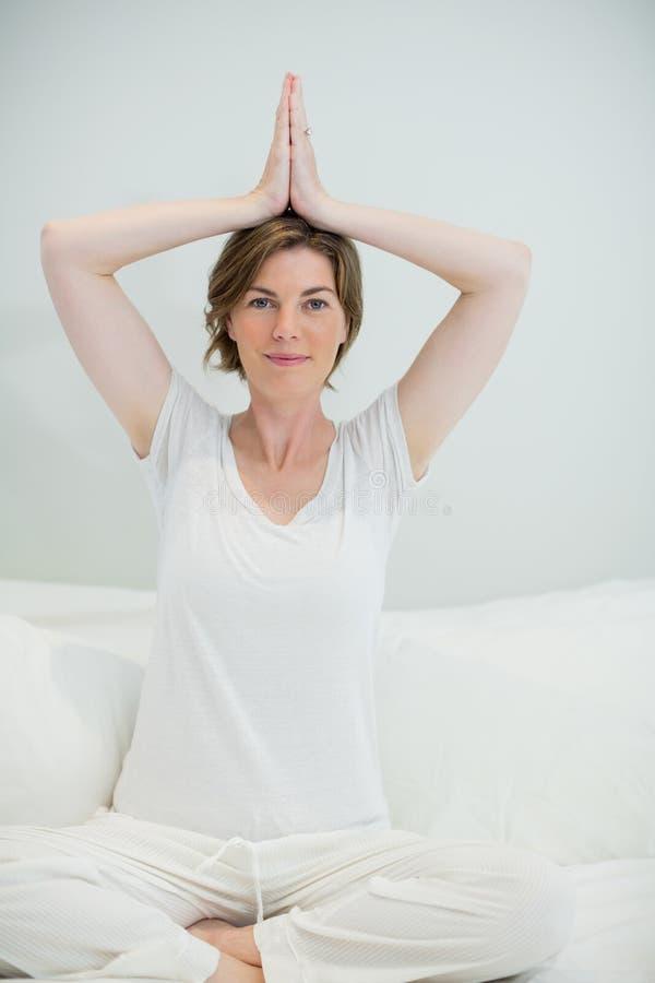 La mujer sonriente que hace yoga ejercita en cama en dormitorio en casa imágenes de archivo libres de regalías