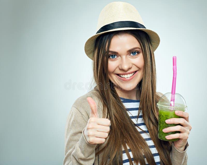 La mujer sonriente que lleva a cabo la bebida del smoothie muestra el pulgar para arriba imagen de archivo libre de regalías