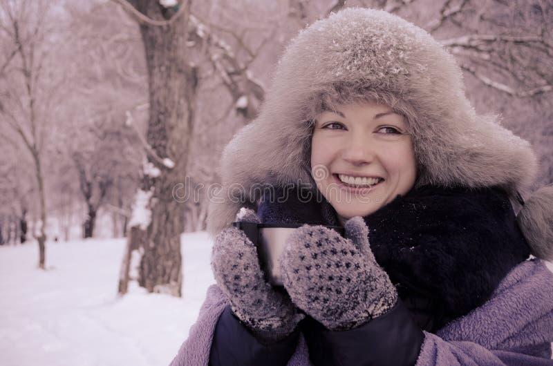 La mujer sonriente que lleva a cabo un viaje asalta en invierno imagenes de archivo