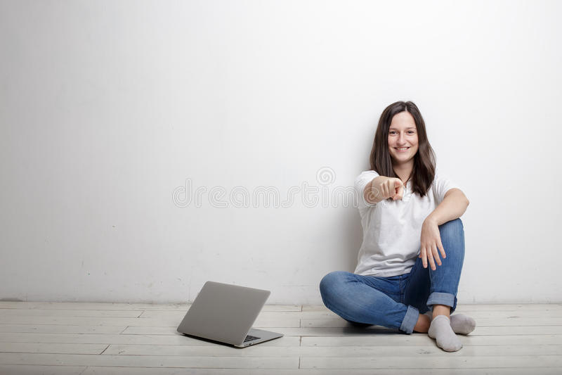 La mujer sonriente señala un finger en usted sentada feliz por la pared o foto de archivo libre de regalías