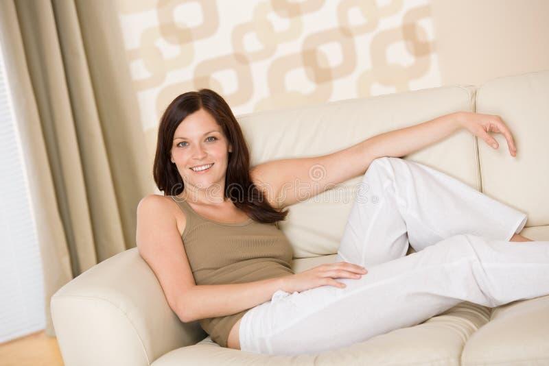 La mujer sonriente se relaja en el sofá en salón fotografía de archivo
