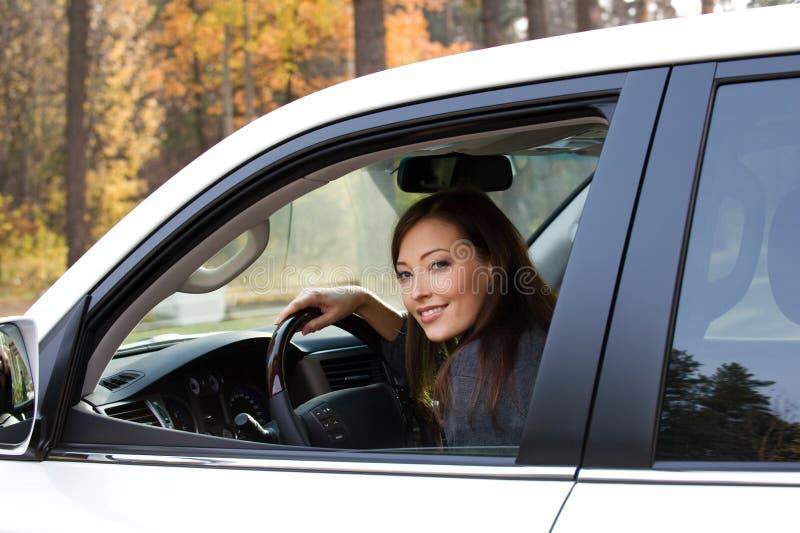 La mujer sonriente se sienta en el nuevo coche imagen de archivo