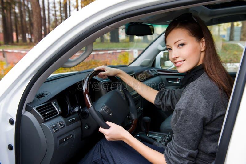 La mujer sonriente se sienta en el nuevo coche foto de archivo