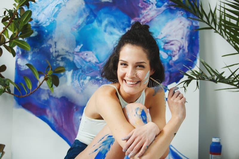 La mujer sonriente sucia de las pinturas se sienta en el fondo de la pared foto de archivo