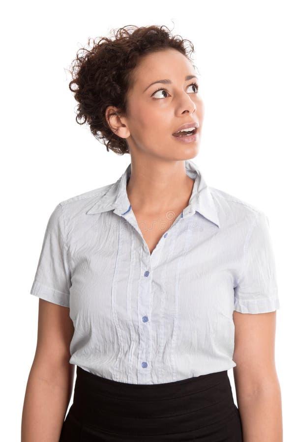 La mujer sorprendió la mirada para arriba curiosamente en el fondo blanco; isolat imagen de archivo libre de regalías