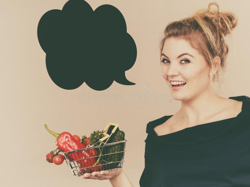 La mujer sostiene la cesta de compras con las verduras, burbuja del discurso fotos de archivo libres de regalías