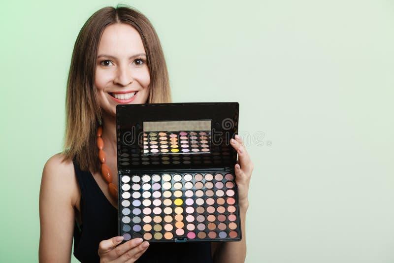 La mujer sostiene la paleta colorida profesional del maquillaje foto de archivo