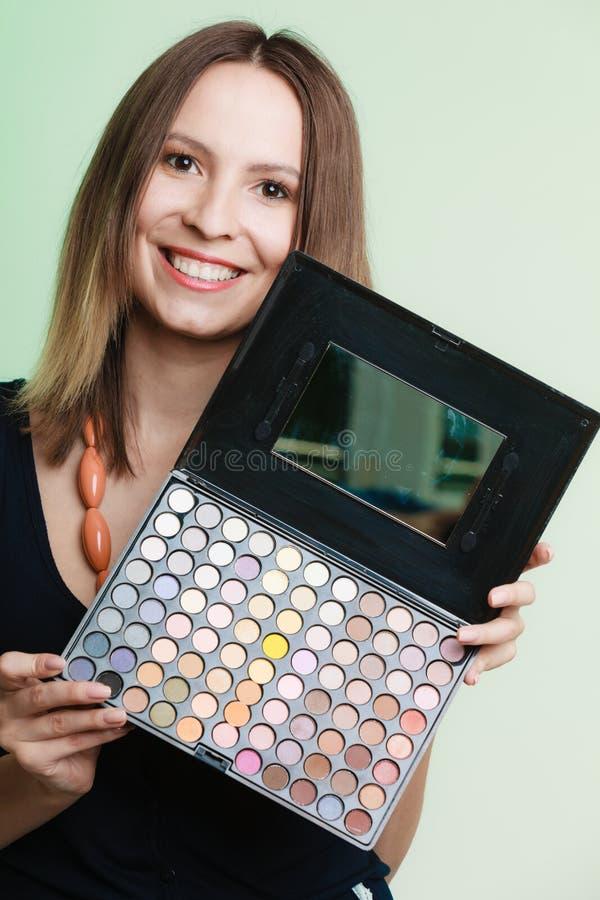 La mujer sostiene la paleta colorida profesional del maquillaje imágenes de archivo libres de regalías